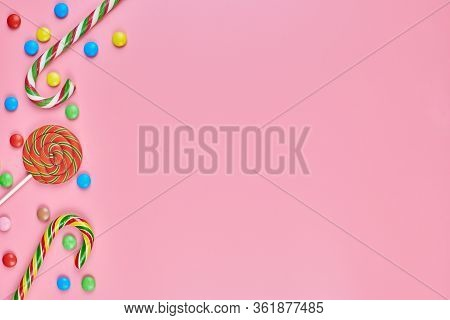 Sweets, Lollipop And Candy Canes On Pink Background, Copy Space. Love To Colorful Sweetmeats In Chil