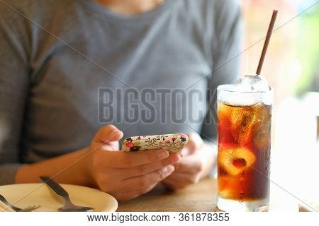 Woman Using Mobile Phone And Glass Of Soft Drink Cola Carbonated With Ice On Wooden Table In Restaur