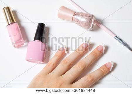 A Woman Glues Stickers On Her Nails For French Manicure. The Girl Applies Nail Polish. Nail Care. Na