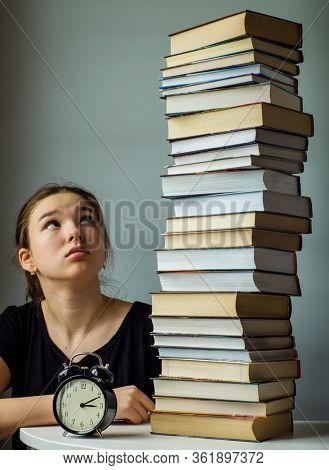 Teenager schoolgirl near a stack of books and an alarm clock. Deadline, self education concept