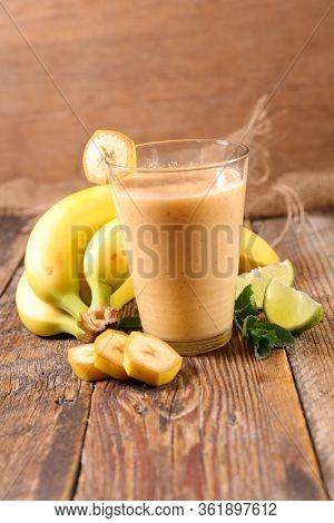 banana smoothie- fruit juice on wood background