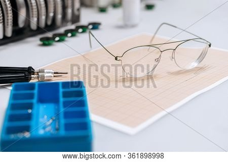 Optician Repairing Equipment And Fixing Eyeglasses. Broken Glasses Laying On Table In Optician Works