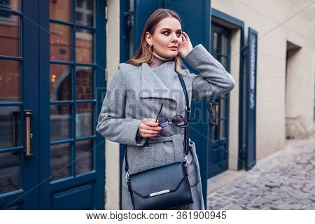 Beauty Portrait Of Stylish Woman Walking Wearing Coat Glasses With Purse On Street. Spring Fashion F