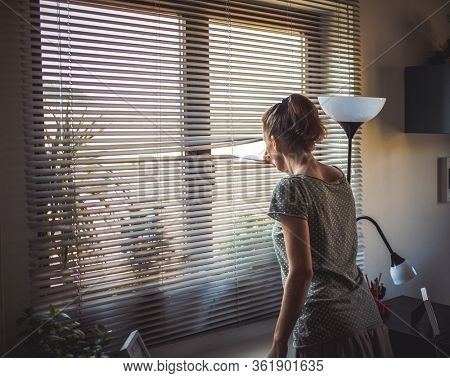 COVID-19 Quarantine mental health. Woman self isolated at home pensive looking out of window thinking of relationship, employment, coronavirus.