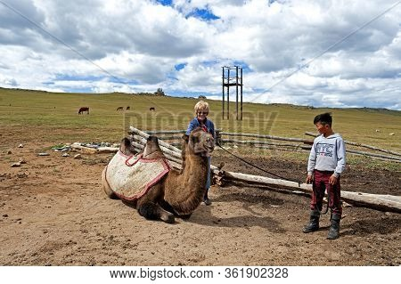 Ulan Bator, Mongolia - August 25, 2016: A Tourist Rides A Camel In The Mongolia 13th Century Nationa