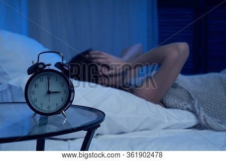 Unhappy woman with insomnia lying on bed next to alarm clock at night