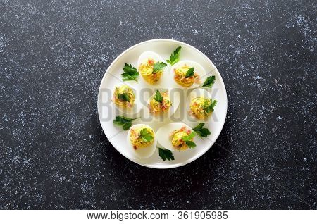 Stuffed Eggs With Egg Yolk, Bacon, Mustard And Parsley On Dark Stone Background With Copy Space. Top