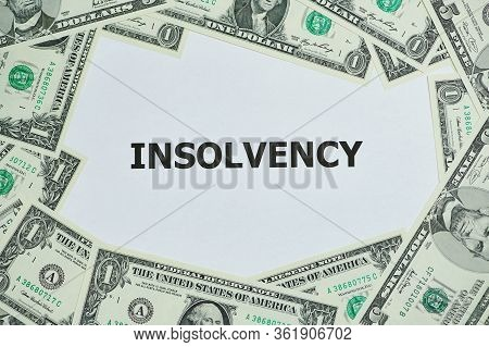 Word Insolvency Printed On A White Paper, Around Are Lying Dollar Bills