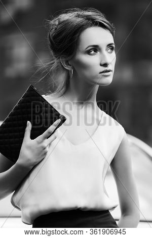 Young business woman with clutch bag on city street Stylish fashion model with bun updo hair style in white sleeveless blouse