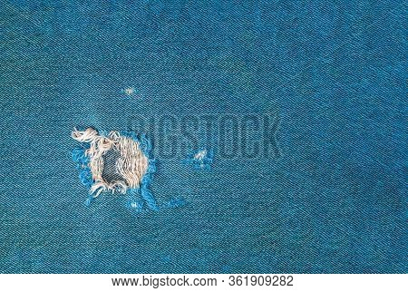 Close Up Of Frayed Hole In Turquoise Denim Fabric