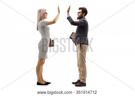 Full length profile shot of a blond young woman teacher holding books and gesturing high-five with a male teacher holding books isolated on white background