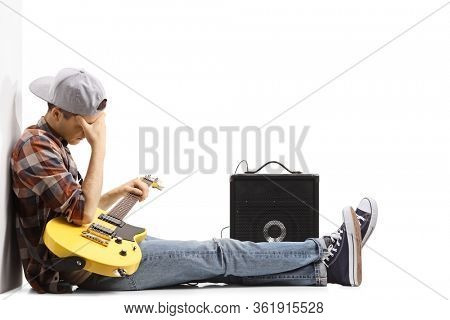 Sad young man sitting on the floor with a guitar isolated on white background