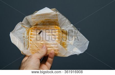 Man Hand Holding Against Pure Gray Background Traditional French Cheese In Paper Packaging
