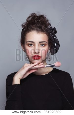 Young beautiful girl with glossy red lips holding makeup brush in her hand