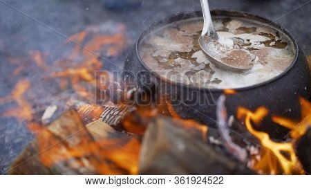 A Pot Of Soup Cooked Over A Fire. Stir Soup With Soup Ladle, Which Is Cooked In A Cast Iron Over A F