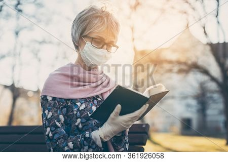 Senior lady praying with face mask reading the bible in front of a church in Covid-19 times