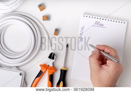 Electrical Engineer At Construction Site. Electrician Write Plan Of Electrical Work. Top View.