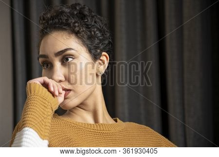 A Woman With Short Hair With A Complentative Expression