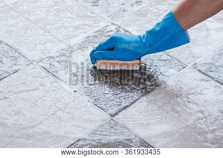 Hand Of Man Wearing Blue Rubber Gloves Is Used To Convert Scrub Cleaning On The Tile Floor.