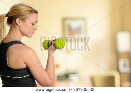 Young beautiful woman workingout inside her livingroom at home