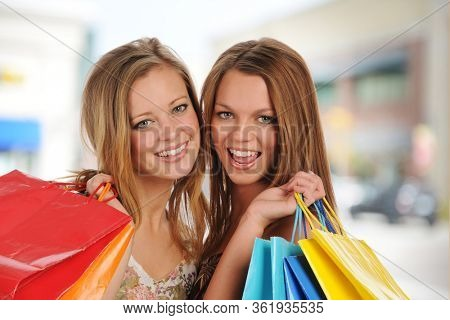 Young beautiful women with shopping bags outside a mall