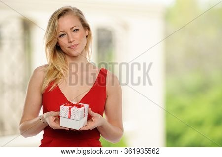 Young beautiful woman holding a gift with house on the background