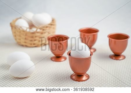 An Eggs Into A Cooper Eggs Cup And Three More Empty Cooper Eggs Cup Behind It, Two Eggs Beside It.,a
