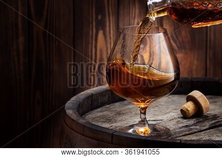 Cognac Pouring Into Snifter Glass With Wave Surface Level On Old Wooden Barrel As Table