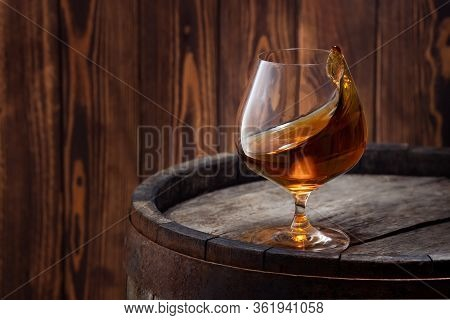 Brandy Or Cognac In Snifter Glass With Wave Surface Level On Old Wooden Barrel As Table