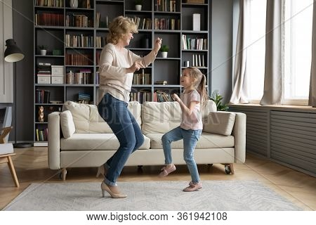 Lively Aged Grandmother Dancing With Little Granddaughter At Home