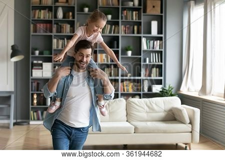 Jovial Father Holding On Shoulders Little Daughter Having Fun Indoors
