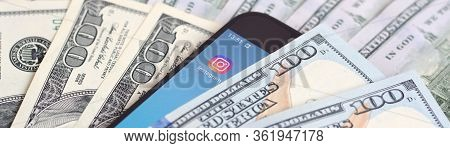 Smartphone Screen With Instagram App And Lot Of Hundred Dollar Bills. Business And Social Networking