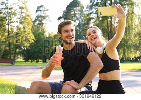 Young Sporty Couple In Sportswear Sitting On Parapet In Urban Park And Taking Selfie After Workout O