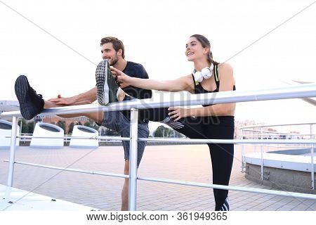 Sporty Couple Of Runners Stretching Leg Muscle, Warming Up Before Running Outdoors For Athlete Train