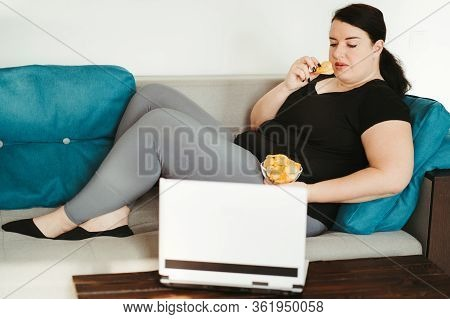 Overeating And Gluttony Concept. Mindless Snacking, Home Sedentary Lifestyle. Obese Woman Sitting On