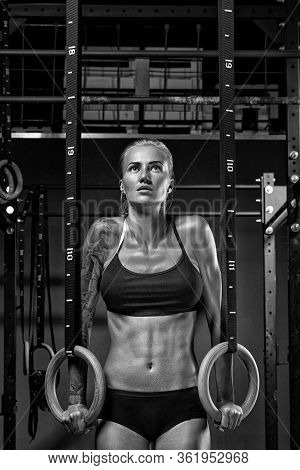 Female Crossfit Caucasian Athlete In Black Sportswear Exercising On Gymnastic Rings At Gym Exercisin