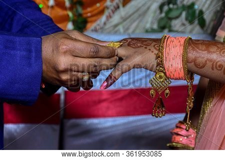 Engagement Ceremony; Indian Groom Putting A Wedding Engagement Ring On Finger Of Bride.