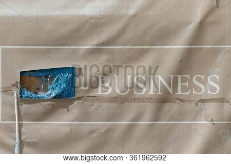 Uzhgorod, Ukraine - April 9, 2020: Hole In The Banner With The Inscription Business On The Fence Of