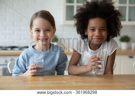 Portrait Of Small Multiracial Girls Drink Mineral Water