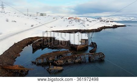 Aerial View Of Winter Snowy Sea Coast With Ruined Boats After The Shipwreck. Footage. Old Sunken Fis
