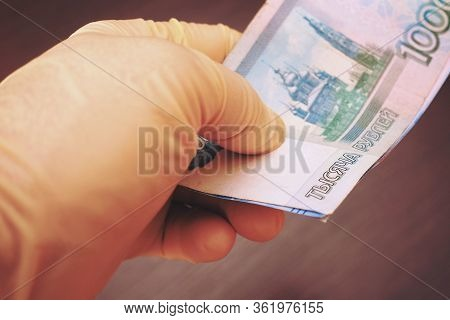 A Hand In A Colorless Medical Latex Glove Holds Out Russian Money. Above Is A 1000 Rubles Banknote.