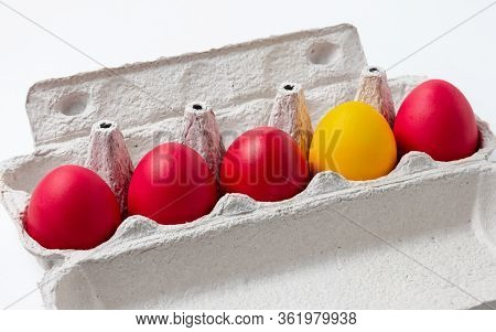 Painted Red And One Yellow Easter Eggs In A Row In A Paper Tray. The Concept Of Individuality, Dissi