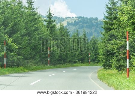 Asphalt Mountain Road Curve With Red And White Snow Poles Against High Pinewood Hills And Cloudy Blu