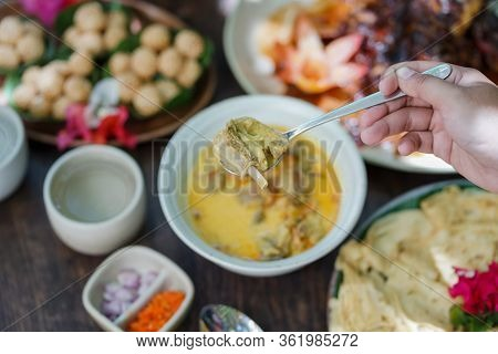Goat Curry Is Served In A Ceramic Bowl On A Wooden Table During A Garden Party.
