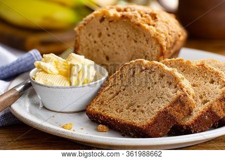 Closeup Of Sliced Banana Nut Loaf Cake And Butter On A Plate With A Bunch Of Bananas In Background