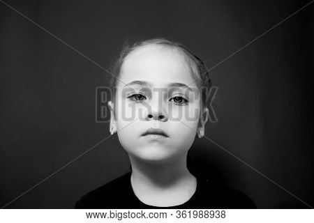 Black And White Photo Portrait Of A Girl Who Looks At The Camera With Sadness.
