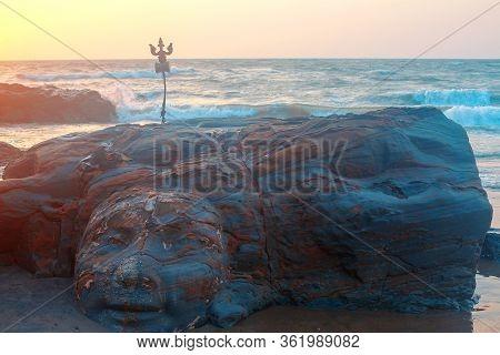 Shiva Face Rock Carving And Trident Totem On Vagator Beach, Goa, India. Beautiful Sunset Background.