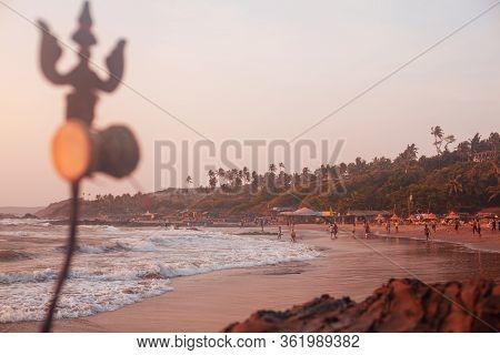 Trident Totem Near Shiva Face Rock Carving On Vagator Beach, Goa, India. Beautiful Sunset And Shore