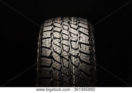 All Terrain New Tire For Off-road And Off-road Vehicles And Crossovers Close-up On A Black Backgroun