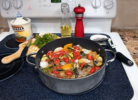 Stove Top With Vegetable Stew In Frying Pan And Cutting Board With Garlic And Herbs